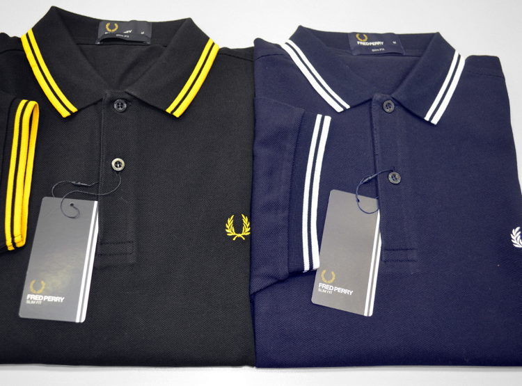 Polo slim fit, manica corta, due bottoni Fred Perry in piqué di cotone: versione slim fit della classica polo Twin Tipped 5-4-4 di Fred Perry, caratterizzata dal colletto leggermente più piccolo. Colori: nero-giallo brillante-giallo brillante, blu-porcellana-porcellana