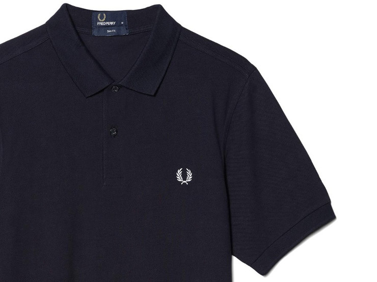 Polo 'one-colour' Fred Perry: polo slim fit, in leggero piqué di cotone tinta unita; con colletto e polsini sono a costine, finta in rilievo a due bottoni e alloro ricamato in contrasto. Variante blu navy