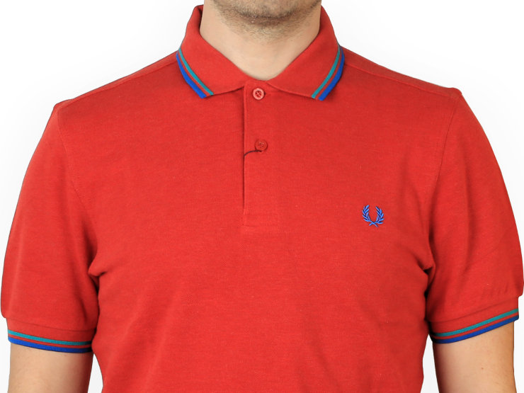 Polo slim fit, manica corta Fred Perry in morbido piqué di cotone, con colletto e polsini a costine twin tipped e con finta in rilievo a due bottoni. Il tipping è l'ormai definitivo 5-4-4, con alloro in tono