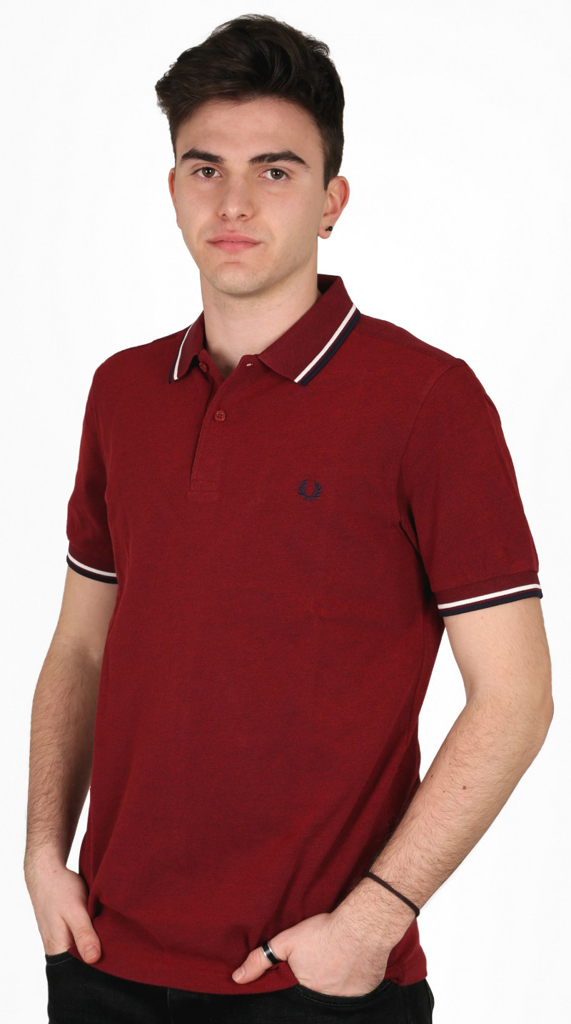 Polo 'classica' Fred Perry: manica corta, due bottoni, in piqué di cotone con tipping doppio 5-4-4 sul colletto e sui polsini; la variante di colore mostrata qui è la bramble blood oxford / white / navy